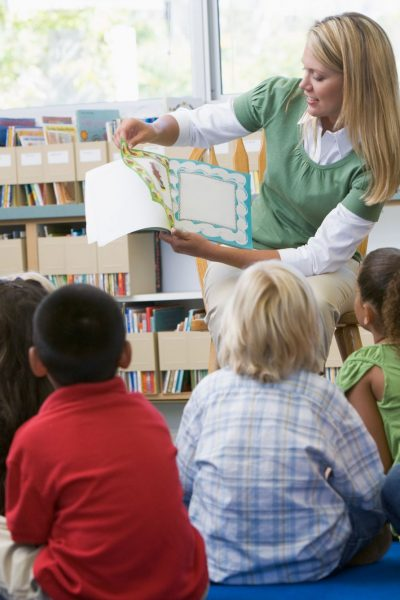 teacher reading book to young children. 50 must read books for pre-k