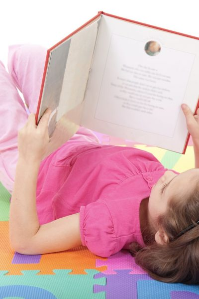 The best way to teach reading - girl lying on floor reading book